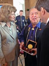 Ozzie Sheakley holds the Congressional Gold Medal While Speaking to Senators Lisa Murkowski and Mark Begich