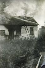 Burning House with a Hose Spraying it Down