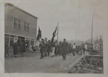 Hoonah Military Marching with Flags in Front of Kanes