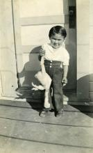 Bill Wolfe, Sr. as a Young Boy holding a Chicken
