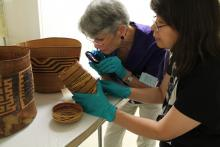 Marjorie Peterson and Daphne Wright Closely Inspecting Baskets